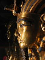 Close up of King Tut's face in shining gold, predates greek architecture element