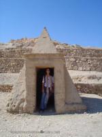 Triangular sand colored stone building with a heavy rectangular opening and a pe